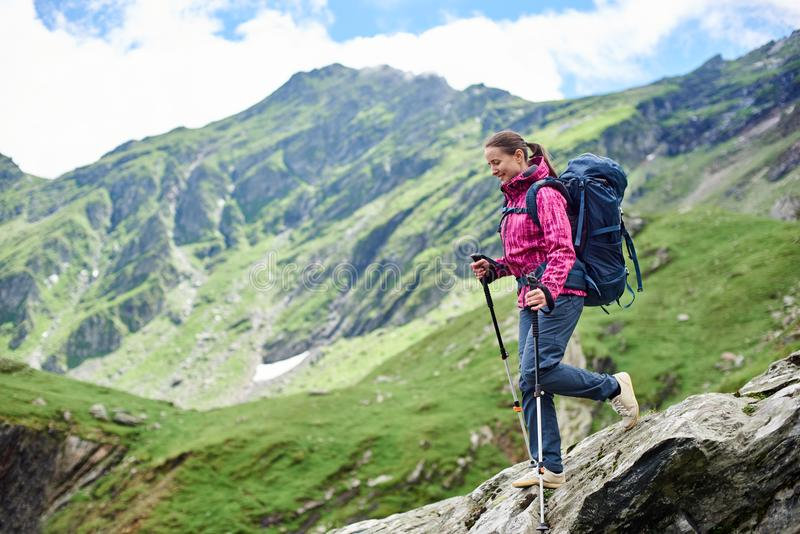 Woman descends the rocky terrain. Young woman with a backpack walking down on the rocky terrain with a blurred view of the mighty green mountains royalty free stock photography