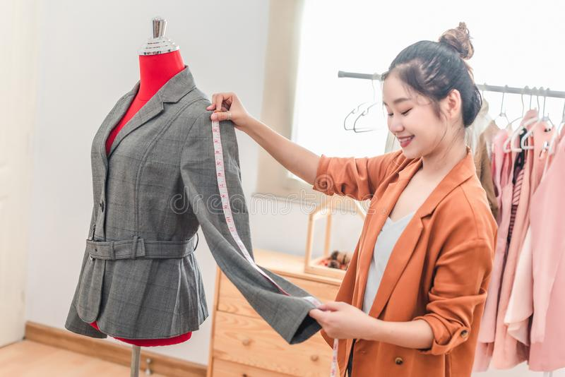 Woman  design measuring the size of clothes at the back of customer by using a measuring tape inside tailor shop royalty free stock photography