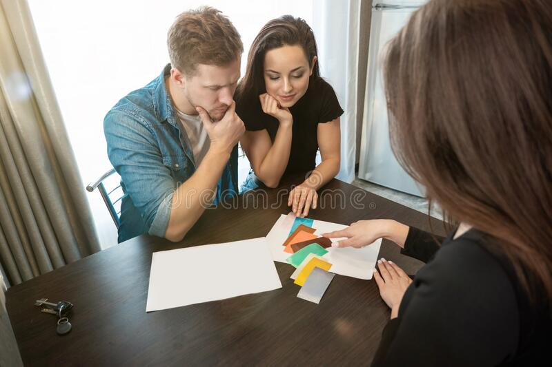 Woman designer consulting young couple husband and wife on wall colours using color palette sitting in new apartment stock photos