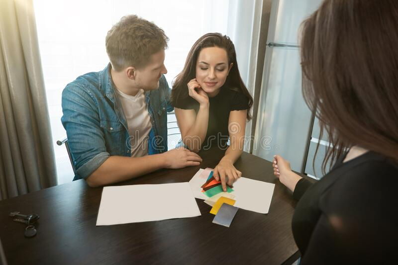 Woman designer consulting young couple husband and wife on wall colours using color palette sitting in new apartment royalty free stock photo