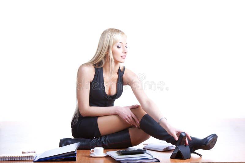 Woman on desk. Woman sitting on office desk stock photo