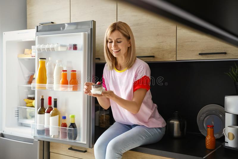 Woman with dessert near refrigerator. In kitchen stock image