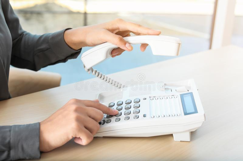 Woman dialing number on telephone stock photos