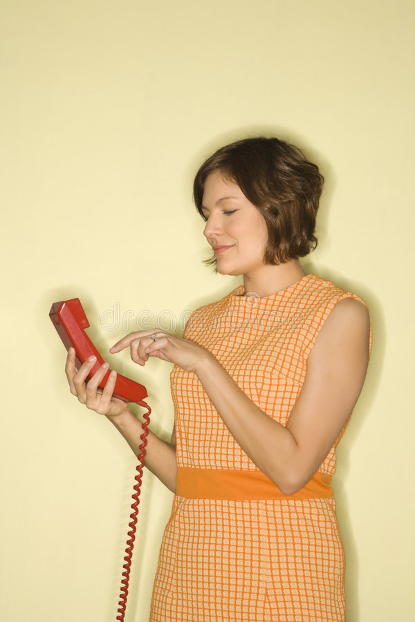 Woman dialing telephone. stock image