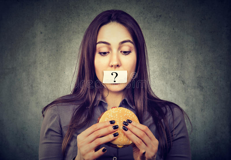 Woman on diet restriction with question mark on mouth looking at burger. Woman on diet restriction with question mark on her mouth looking at tasty burger on royalty free stock photography