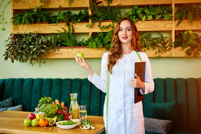 Woman dietitian in medical uniform with tape measure holds apple standing with different healthy food ingredients in the green royalty free stock image