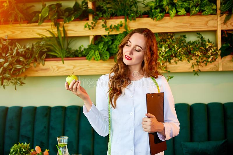 Woman dietitian in medical uniform with tape measure holds apple standing with different healthy food ingredients in the green royalty free stock photo