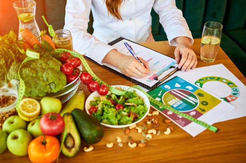 Woman dietitian in medical uniform with tape measure working on a diet plan sitting with different healthy food ingredients in the. Green office on background stock images