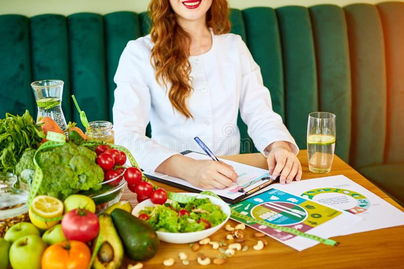 Woman dietitian in medical uniform with tape measure working on a diet plan sitting with different healthy food ingredients in the. Green office on background royalty free stock photos
