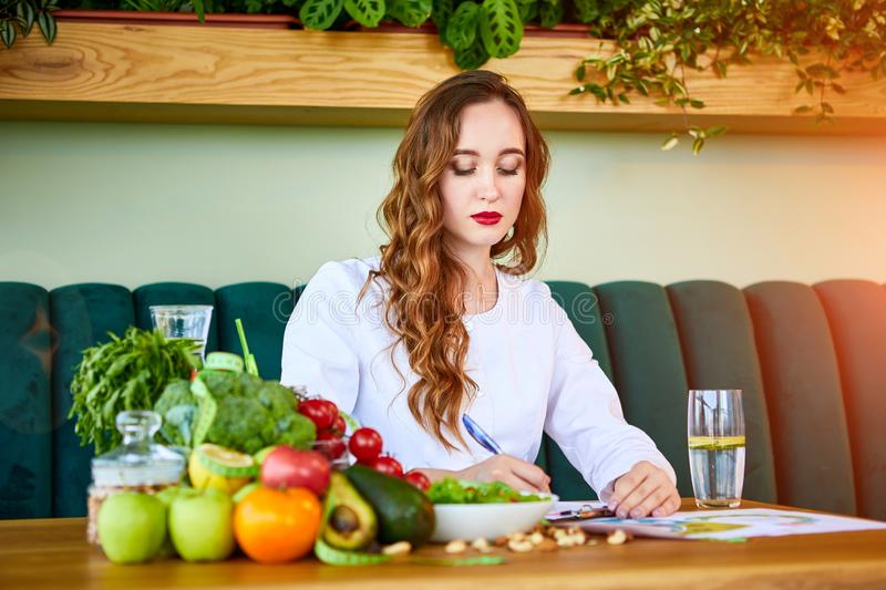 Woman dietitian in medical uniform with tape measure working on a diet plan sitting with different healthy food ingredients in the. Green office on background royalty free stock images