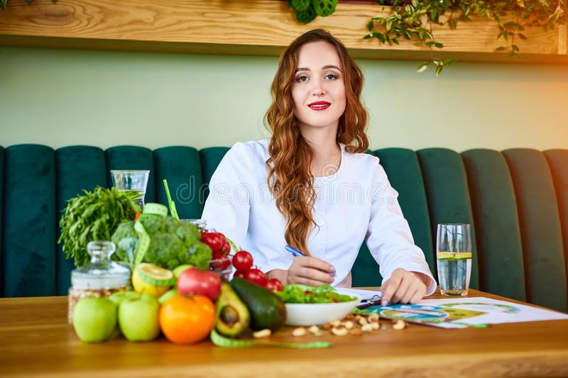 Woman dietitian in medical uniform with tape measure working on a diet plan sitting with different healthy food ingredients in the. Green office on background stock photography