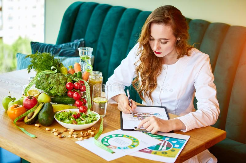 Woman dietitian in medical uniform with tape measure working on a diet plan sitting with different healthy food ingredients in the. Green office on background royalty free stock image