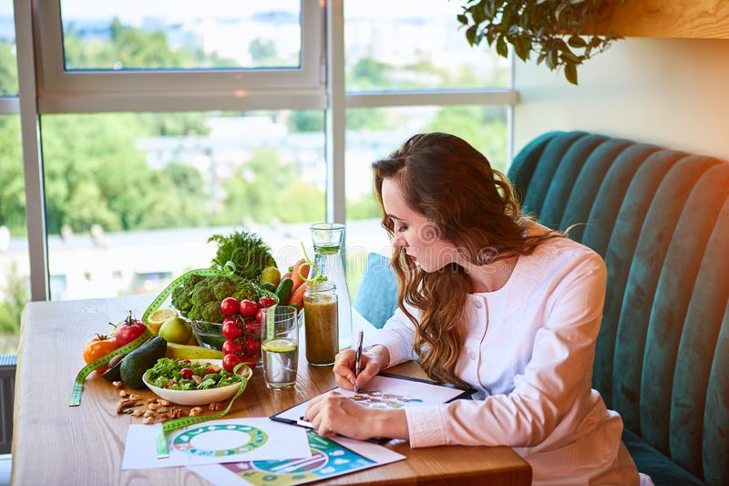 Woman dietitian in medical uniform with tape measure working on a diet plan sitting with different healthy food ingredients in the stock photo