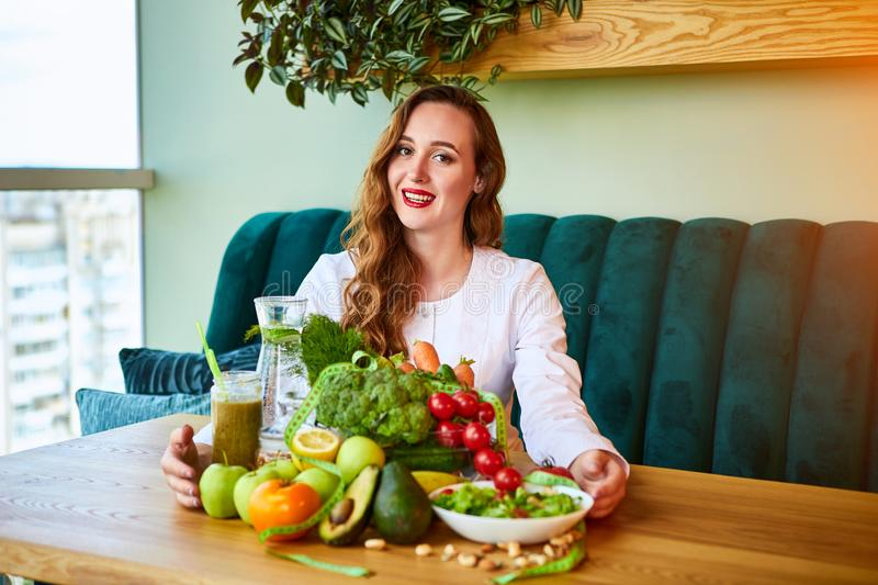 Woman dietitian in medical uniform with tape measure working on a diet plan sitting with different healthy food ingredients in the stock image