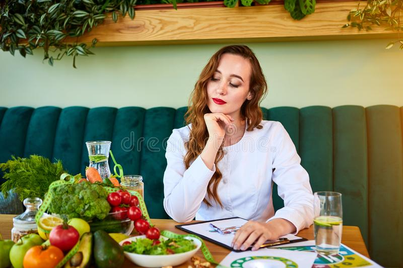 Woman dietitian in medical uniform with tape measure working on a diet plan sitting with different healthy food ingredients in the stock photography