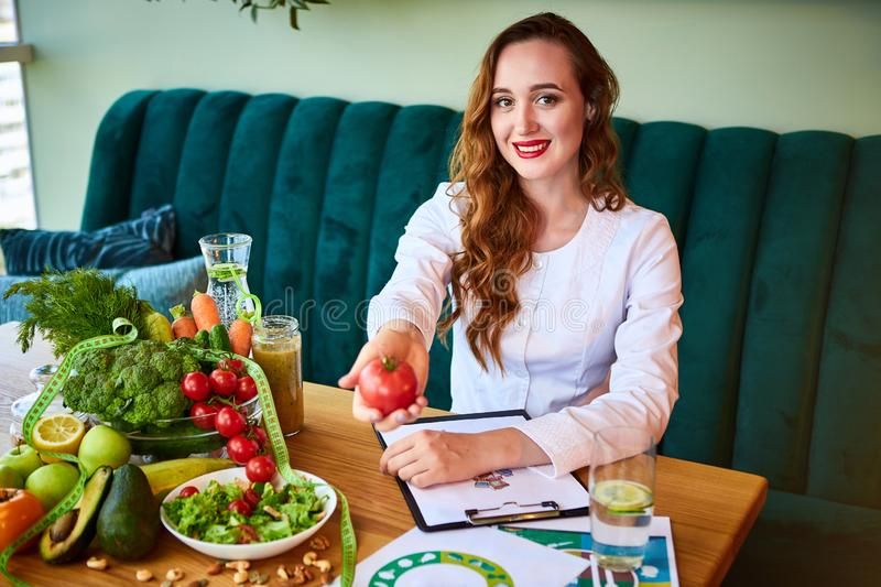 Woman dietitian in medical uniform with tape measure working on a diet plan sitting with different healthy food ingredients in the stock images