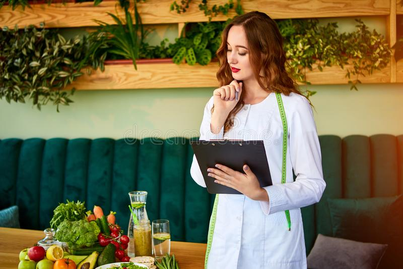 Woman dietitian in medical uniform with tape measure working on a diet plan standing with different healthy food ingredients in. The green office on background royalty free stock photos