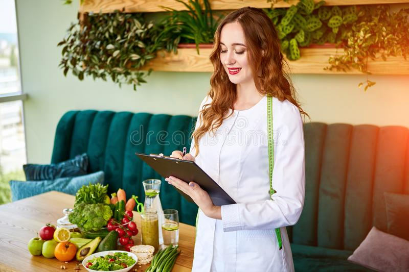 Woman dietitian in medical uniform with tape measure working on a diet plan standing with different healthy food ingredients in. The green office on background royalty free stock image