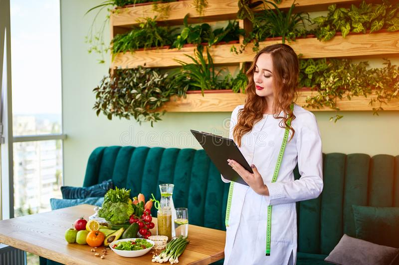 Woman dietitian in medical uniform with tape measure working on a diet plan standing with different healthy food ingredients in. The green office on background stock images