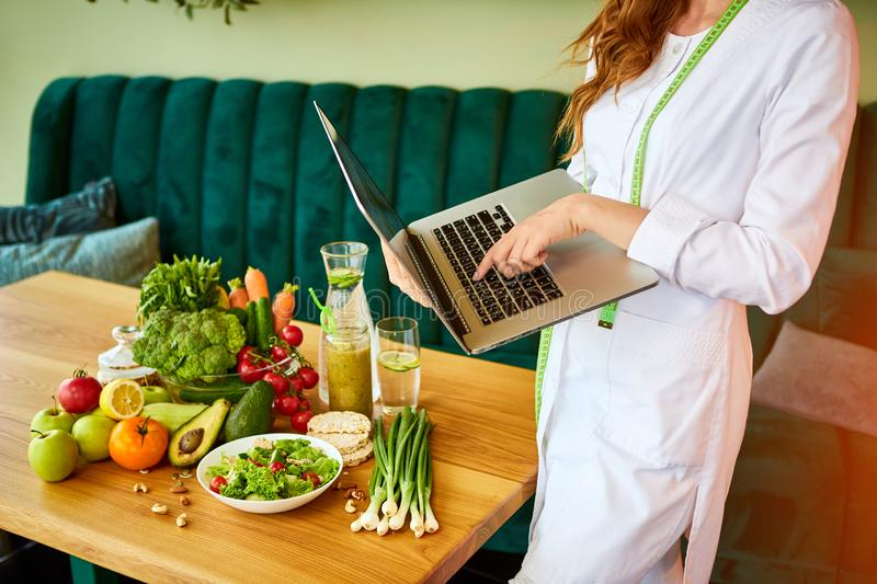 Woman dietitian in medical uniform with tape measure working with laptop on a diet plan standing near different healthy food. Ingredients in the green office on royalty free stock image