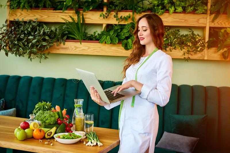 Woman dietitian in medical uniform with tape measure working with laptop on a diet plan standing near different healthy food. Ingredients in the green office on royalty free stock photography