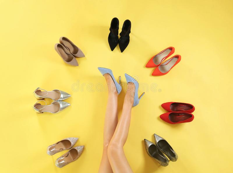 Woman and different high heel shoes, top view. Woman and different high heel shoes on yellow background, top view royalty free stock photography