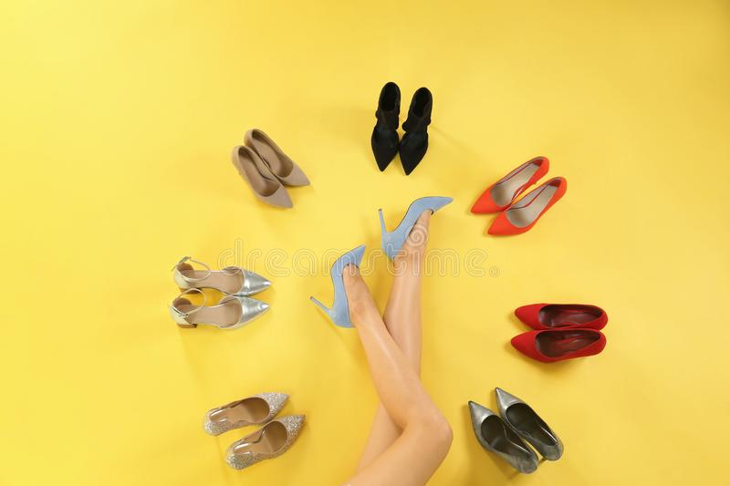 Woman and different high heel shoes on yellow background stock image