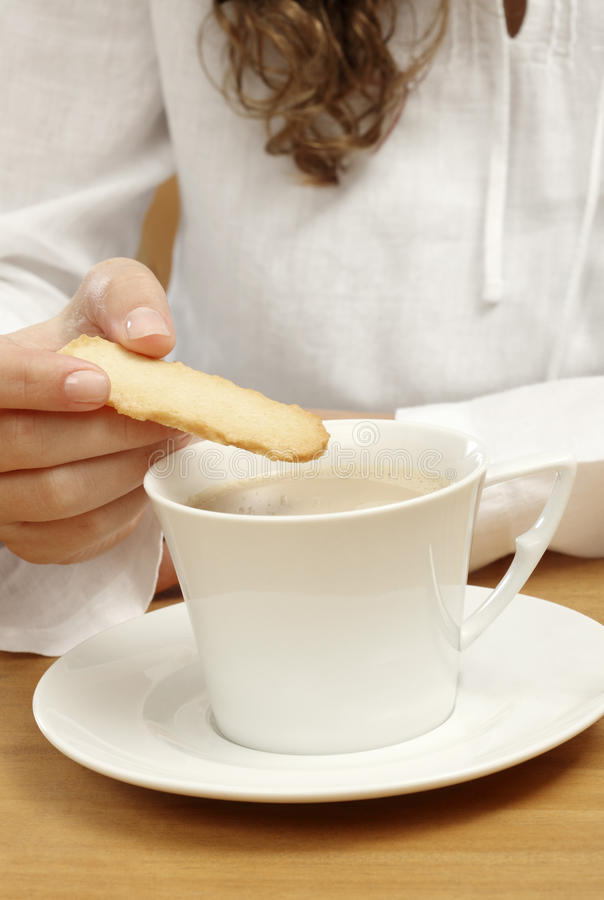 Download Woman Dipping A Cookie In A Cup Of White Coffee Stock Photo - Image: 23702930