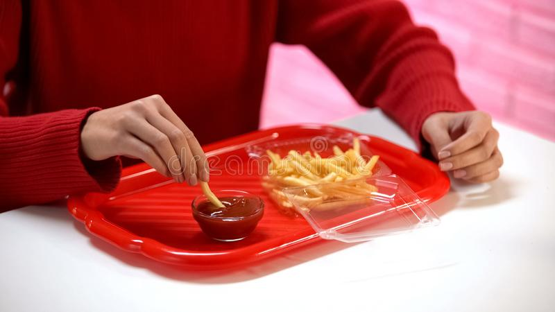 Woman dipping french fry in ketchup, unhealthy nutrition, fast food restaurant stock images