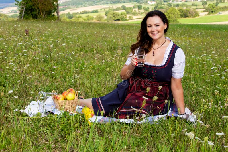 Woman in dirndl sitting on blanket in meadow and drinking water stock images