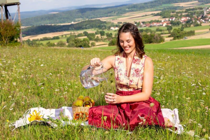 Woman in dirndl sitting on blanket in meadow and drinking water. Young woman in dirndl sitting on blanket in meadow and drinking water royalty free stock image