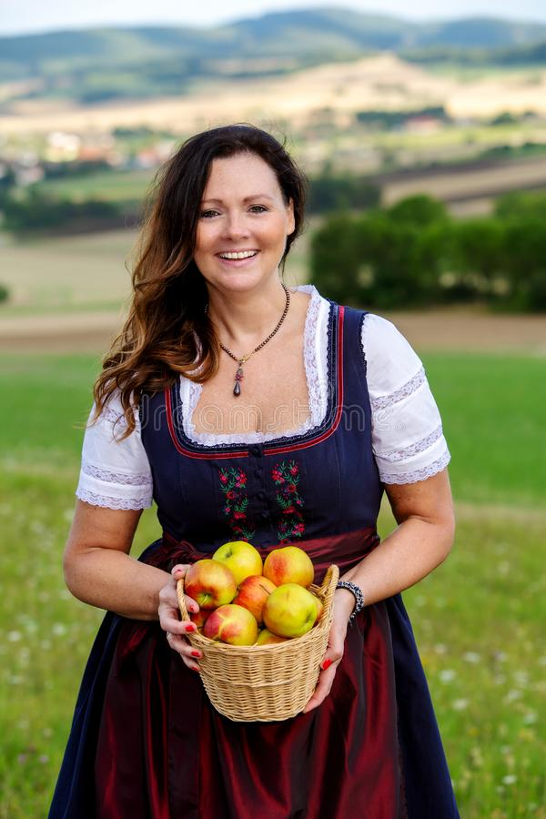 Woman in dirndl standing in meadow and holding a basket of apples royalty free stock photos