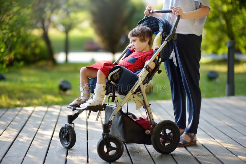 Woman with disabled girl in a wheelchair walking in the Park summer. Child cerebral palsy. Family with disabled kid. Woman with disabled girl in a wheelchair stock photo