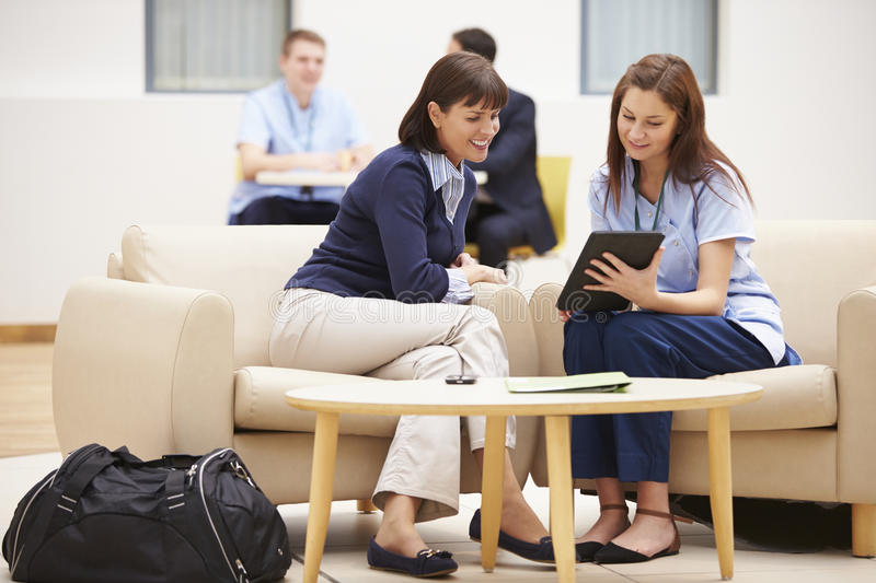 Woman Discussing Results With Nurse On Digital Tablet stock photography