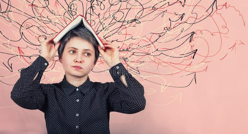 Woman, dissatisfied expression, feels tired of constant learning, keeps open book over head, demands holidays. Difficult task to stock photography