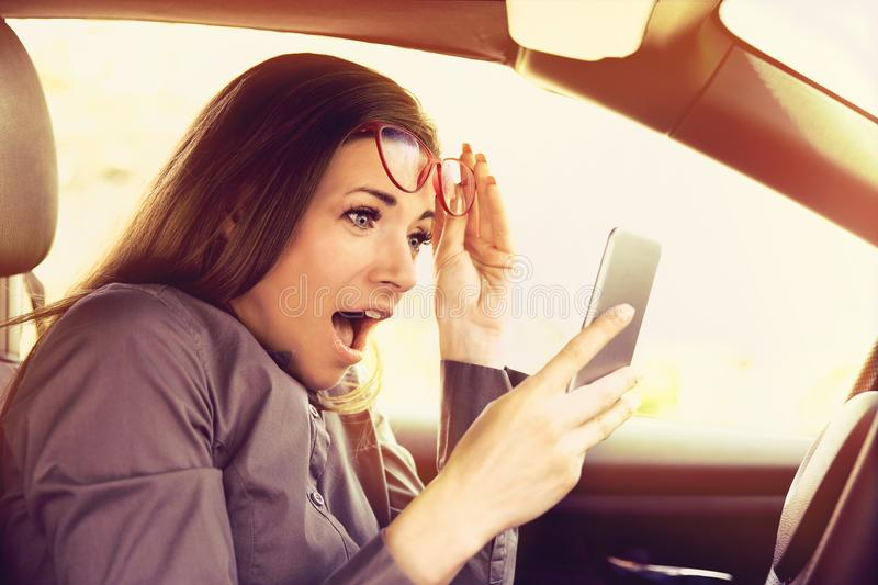 Woman distracted reading a message on cellphone, amazed, while driving a car. Young woman distracted reading a message on cellphone, amazed, while driving a car stock image