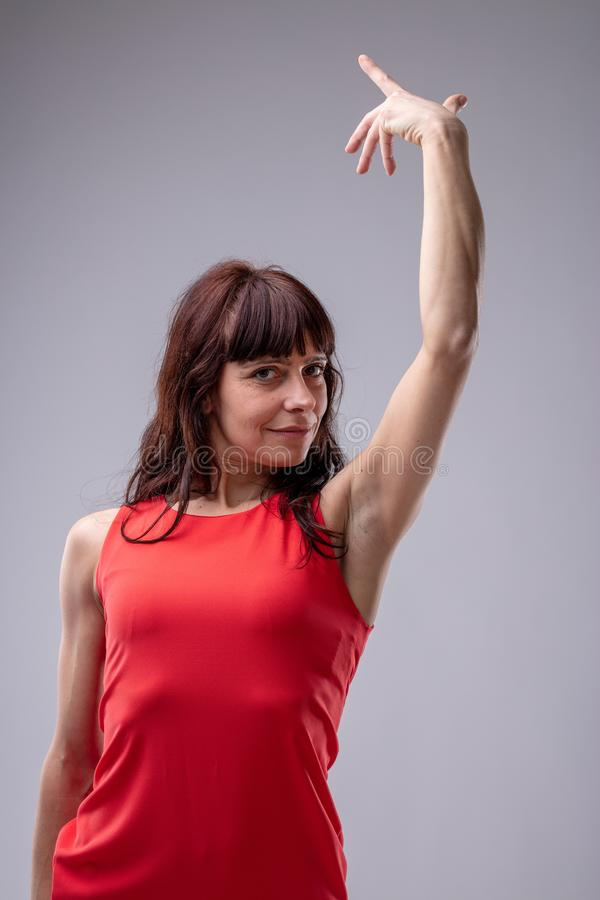 Woman diva gesturing with her hand. Woman diva gesturing gracefully with her hand with a superior smile as she looks down at the camera, low angle over grey stock images