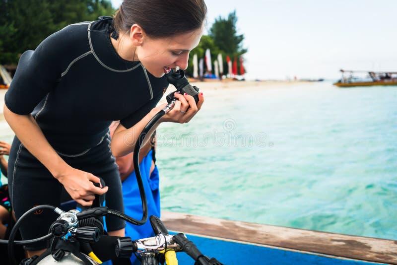 Woman diver testing regulator before scuba diving stock photos