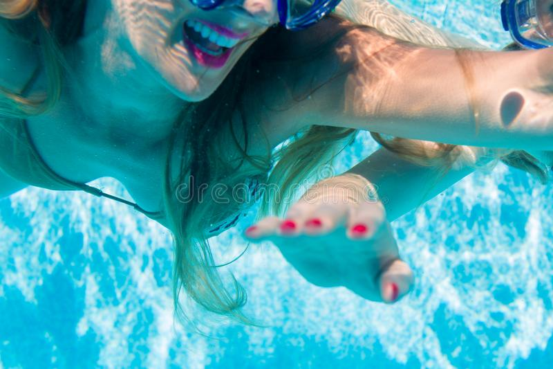 Woman diving underwater in resort swimming pool royalty free stock images