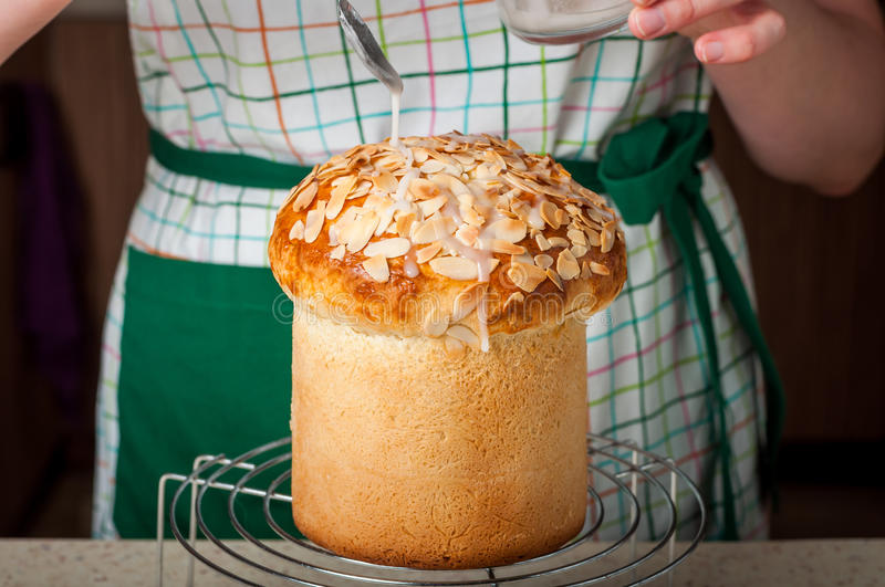 A Woman Dizzling Easter Bread with Sugar Icing. A Woman Wearing Apron Dizzling Easter Bread (Kulich) with Sugar Icing royalty free stock image