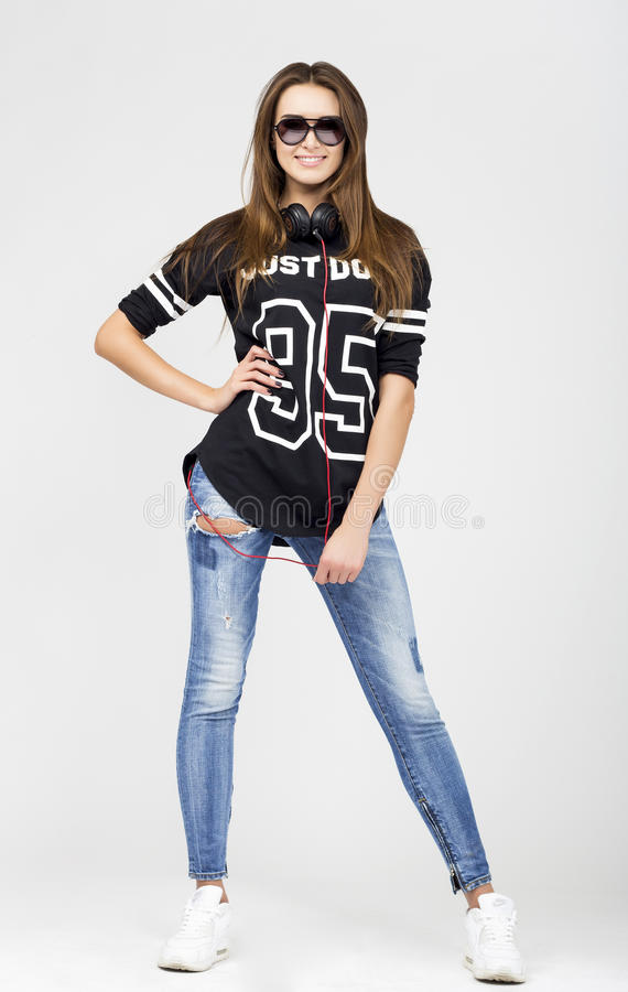 Woman DJ with earphones in jeans and black shirt stock image