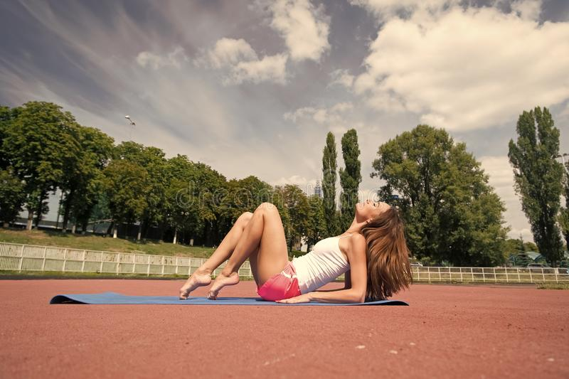 Woman do pilates on yoga mat. Sensual woman relax on stadium. Fashion athlete practice yoga outdoor. Wellness and royalty free stock photography