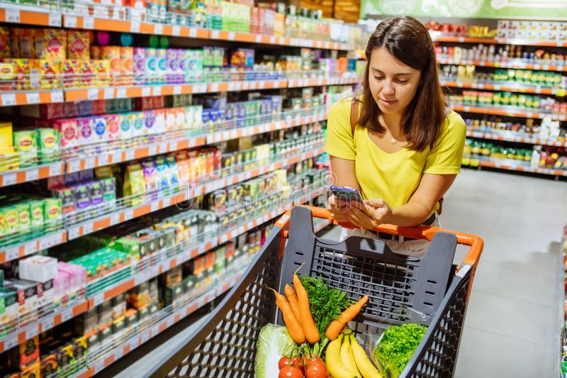 Woman do shopping check to buy list in phone stock image