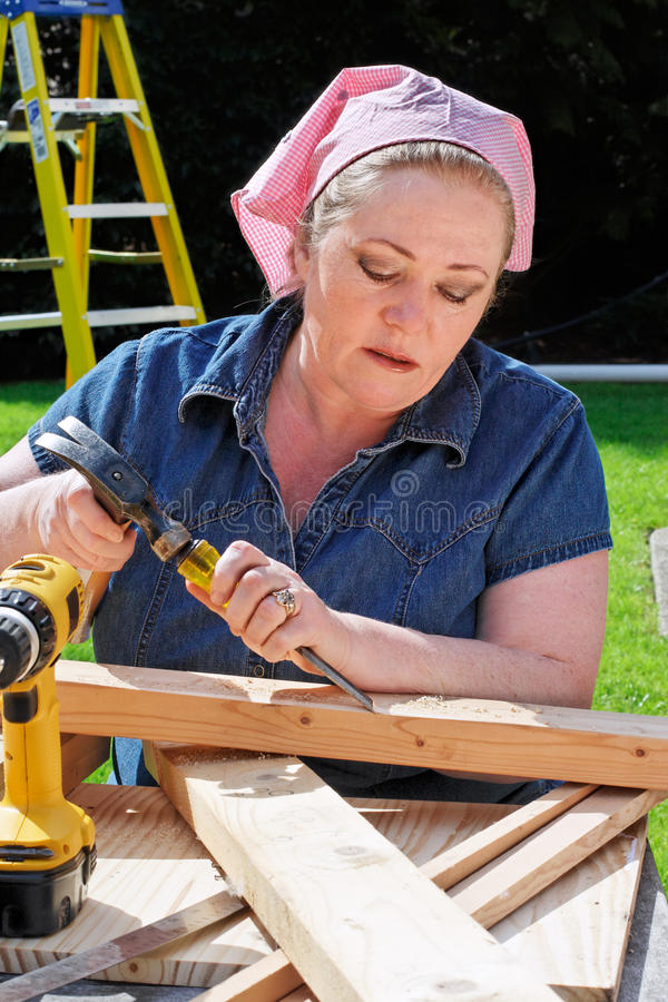 Woman do it yourself project. Mature woman chiseling the edges of piece of lumber stock images