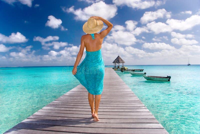 Woman dock sarong. Beautiful woman in blue sarong walks down resort pier