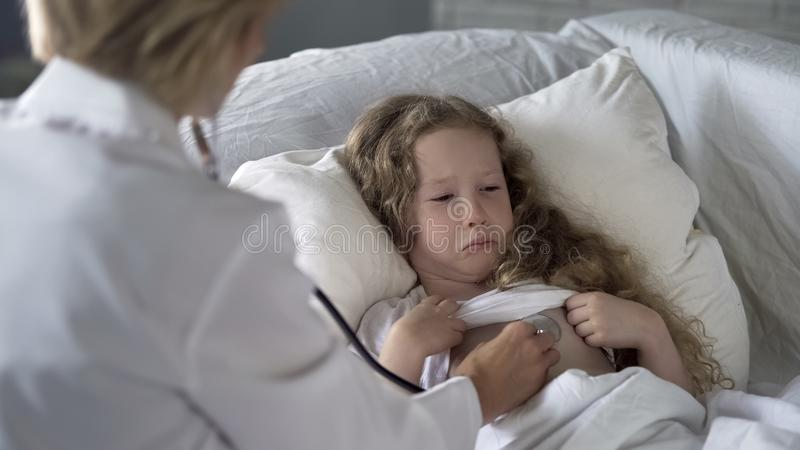 Woman doctor carefully examining sick child with stethoscope, little girl crying stock image