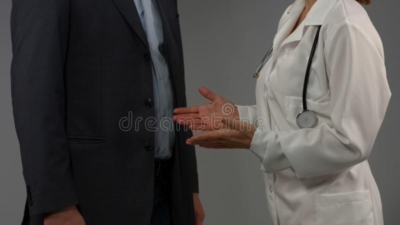 Woman doctor consulting male patient, talking diagnosis, advising medicaments stock image