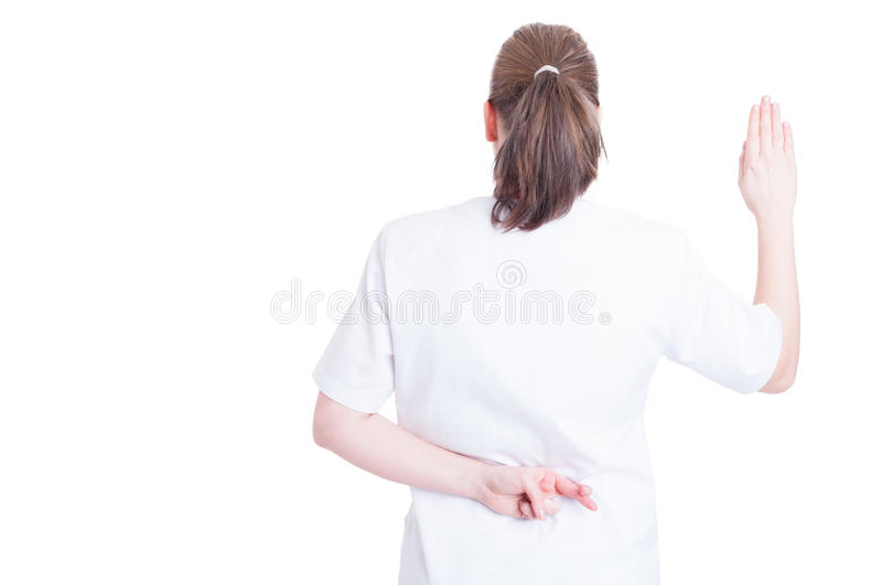 Woman doctor crossing fingers behind her back stock photography