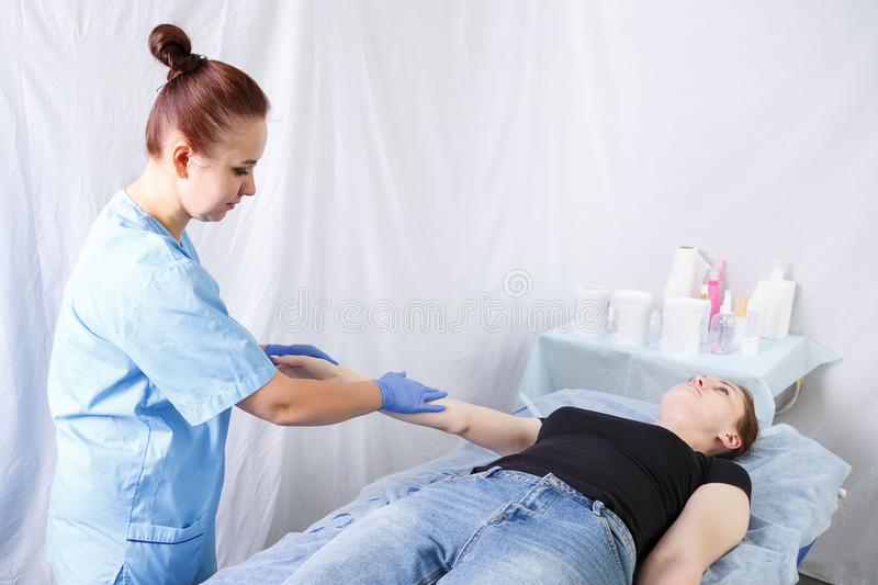 A woman doctor doing a woman`s right hand massage, patient stock photography