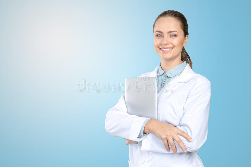 Woman doctor holding laptop. Beautiful young woman doctor holding laptop stock image